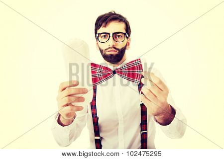 Handsome man wearing suspenders with menstruation pad.