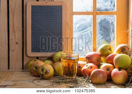 Glass Of Cider With Apples And Small Blackboard
