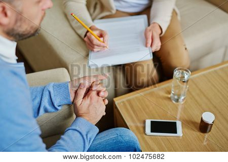 Male sitting in armchair while psychiatrist making notes in medical document