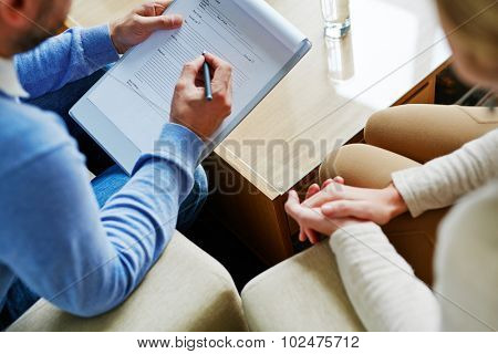 Male psychiatrist making notes with his patient near by