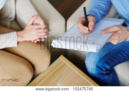 Hands of psychiatrist filling in medical document with patient near by