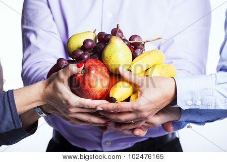 Group of people hands holding apples, oranges, plums and bananas (selective focus)