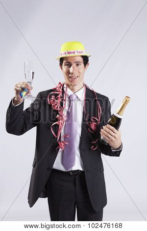 businessman celebrating the new year eve with champagne (isolated on gray)