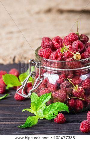 Fresh raspberry in glass jar over dark wooden background