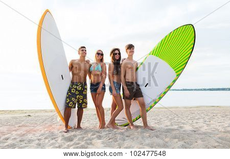 friendship, sea, summer vacation, water sport and people concept - group of smiling friends wearing swimwear and sunglasses with surfboards or stand up paddle boards on beach