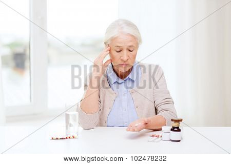 age, medicine, health care and people concept - senior woman with pills and glass of water at home