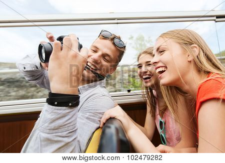 friendship, travel, summer vacation, technology and people concept - group of happy friends with digital camera traveling by tour bus and laughing