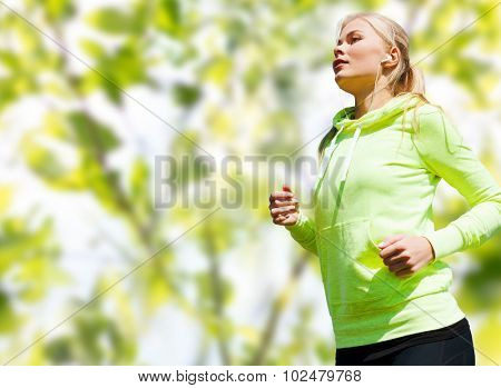 people, sport, fitness and slimming concept - happy woman running or jogging over green leaves background