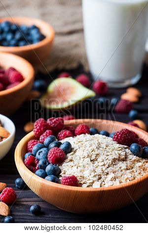 Healthy Breakfast. Bowl of muesli with berries and nuts over dark wooden background. Health and diet concept.