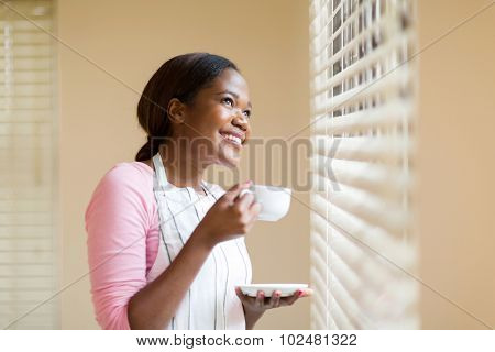 cheerful african american housewife having coffee at home