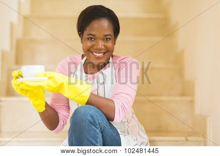 beautiful young african american housewife drinking coffee after housework