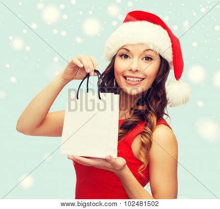 shopping, sale, gifts, christmas, x-mas concept - smiling woman in red dress and santa helper hat with shopping bag