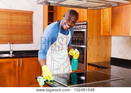 happy african american man cleaning stove