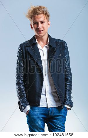 close up with sexy young guy with leather jacket, white shirt and hands in pockets while smiling at the camera