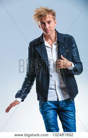 beautiful skinny blonde young man holding his leather jacket while smiling at the camera and waving his hand