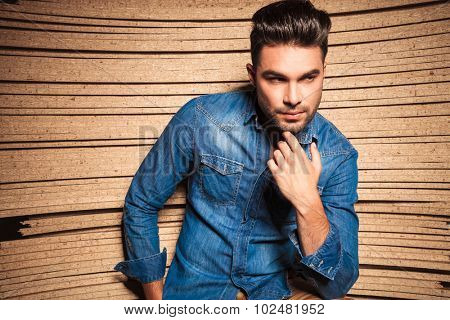 beautiful man touching his chin while leaning against a wooden wall