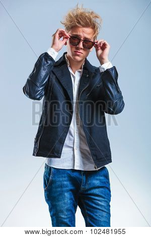 portrait of blonde skinny man wearing jeans and leather jacket while fixing his sunglasses