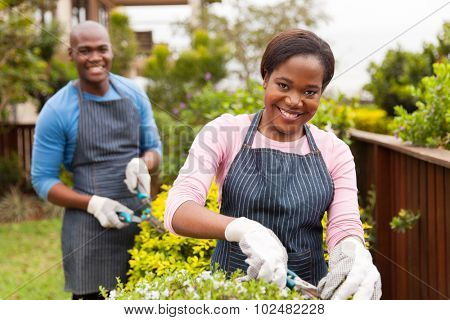 portrait of beautiful young black couple working together in home garden