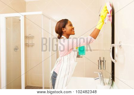 pretty young african woman wiping bathroom mirror at home