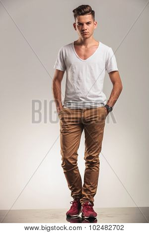 hansome young fashion men standing on studio backgroung with his hands in pockets