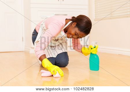 happy young african woman wiping wooden floor