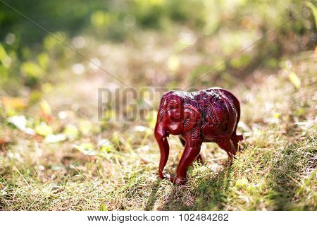 Red figurine of an elephant on grass and beautiful sunset background