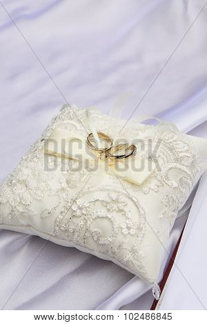 Wedding rings on a white pillow .
