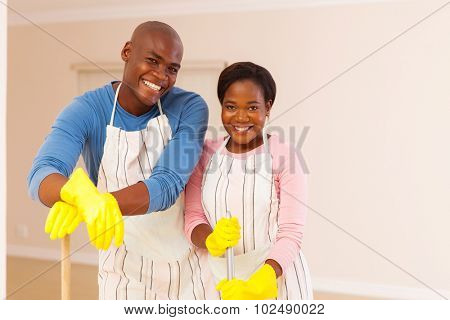 happy african couple cleaning their apartment