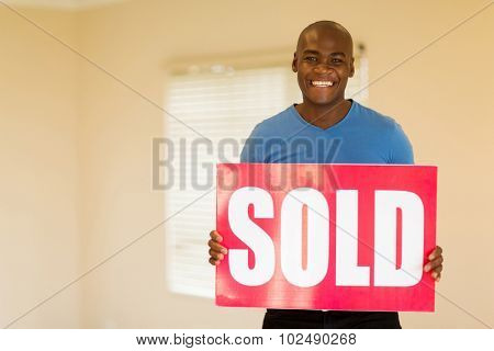 happy young black man holding sold sign in his home