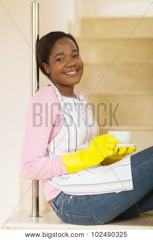 pretty african housewife relaxing at home after housework