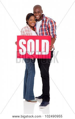 portrait of lovely young african american couple holding a sold sign