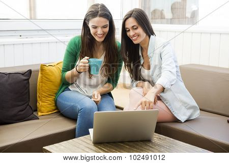 Female friends at the local coffee shop drinking coffee and working