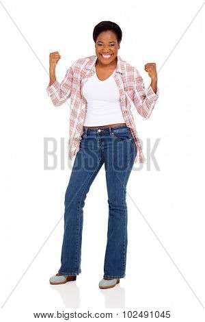 excited young african woman holding fists on white background