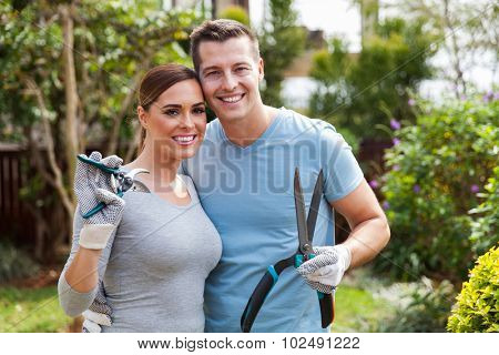 lovely couple holding gardening tools in home backyard