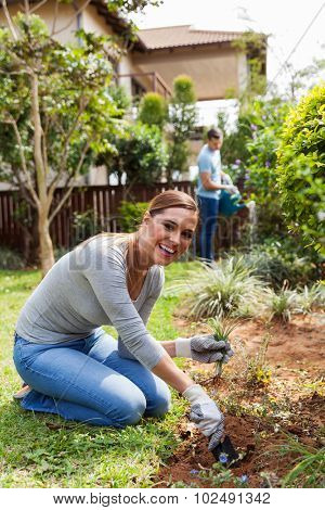 cheerful woman digging a hole before planting with boyfriend on background watering garden