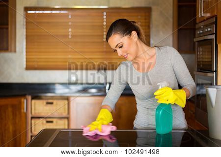 smiling young woman cleaning the stove