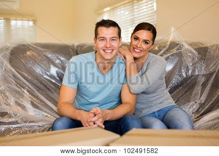 smiling young couple sitting on sofa in their new house