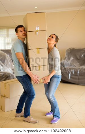 young couple carrying a heavy pile of boxes in their new home