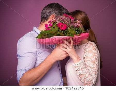kissing behind the floral bouquet on valentines day