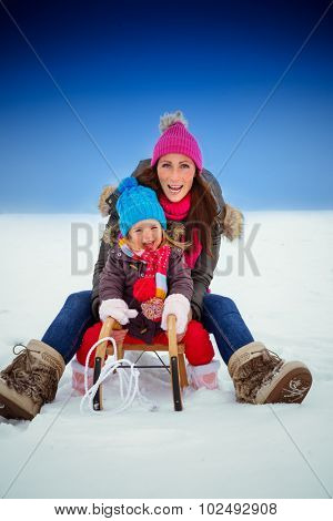 wintertime sliding family having fun