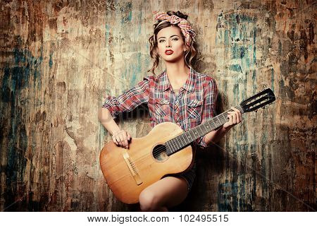 Pretty pin-up girl posing with guitar. Beauty, fashion.