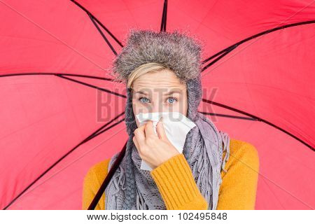 Woman blowing her nose with a tissue under her umbrella