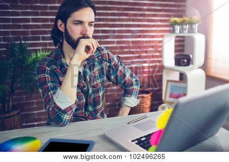 Thoughtful businessman with hand on chin looking using laptop