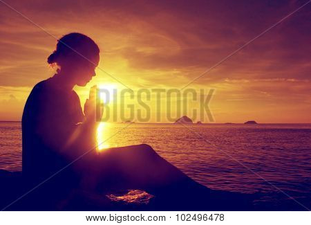 Young woman praying sunset over the Ocean Concept