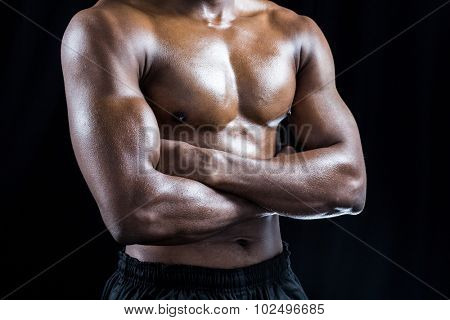 Mid section of shirtless athlete standing with arms crossed against black background