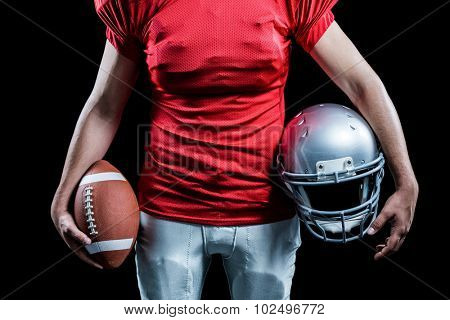 Mid section of sportsman holding American football and helmet against black background