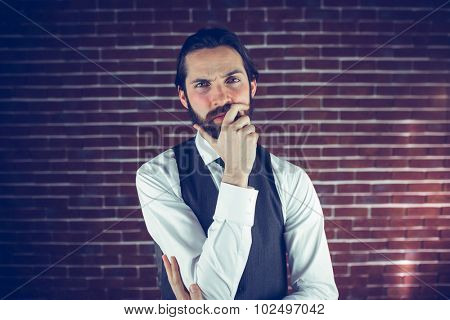 Portrait of serious man with hand on chin against brick wall