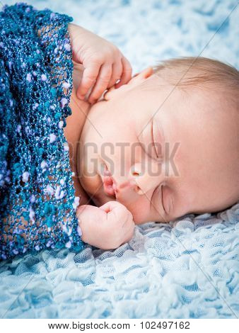 Newborn baby boy asleep wrapped in a blue blanket close up