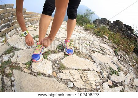 woman runner tying shoelace on china great wall .