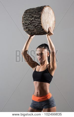 muscular woman holding aloft a log